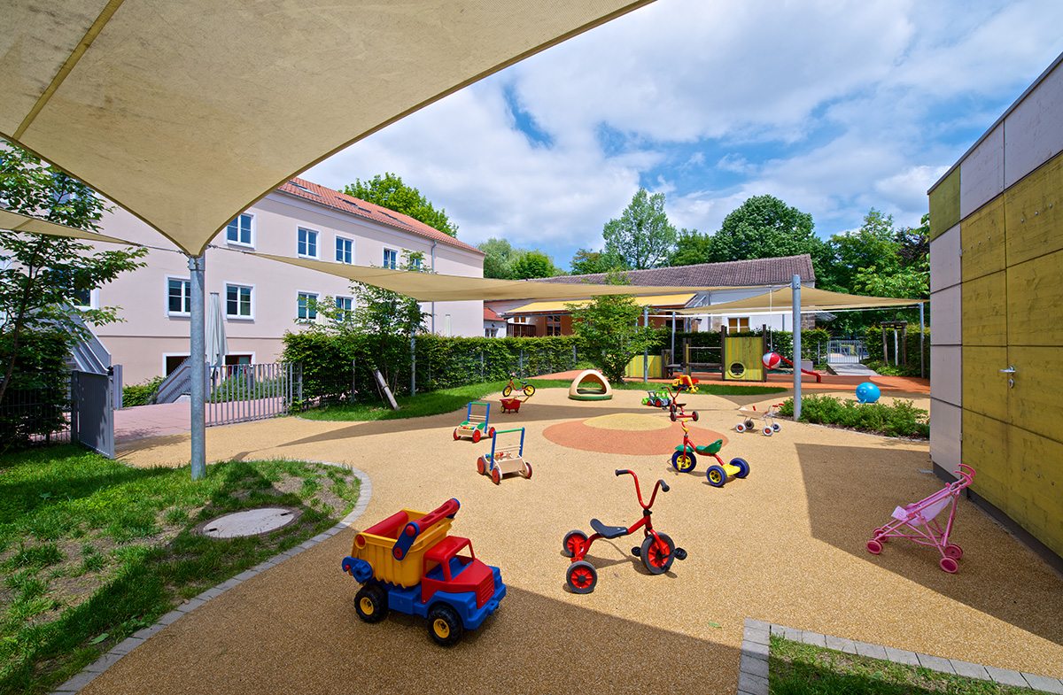 The sunny courtyard of a kindergarten with many toys.