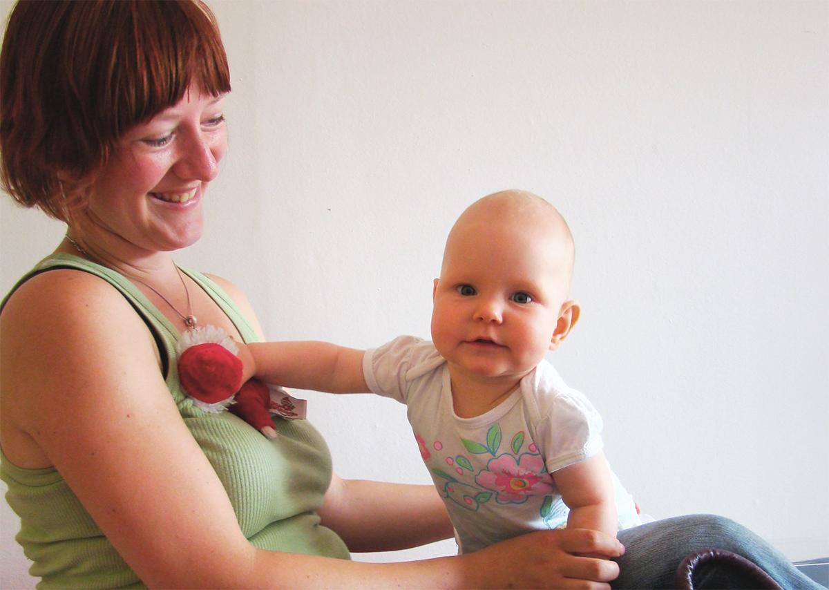 Eine junge Mutter hält lachend ihr Baby in den Armen