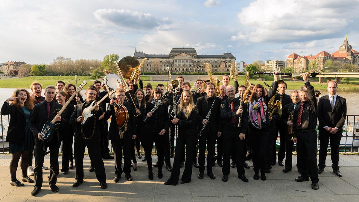 Eine Gruppe von mehr als 30 schwarz gekleideten Personen präsentieren ihre Instrumente. Im Hintergrund ist die Elbe und das Sächsisches Staatsministerium für Kultus zu sehen.