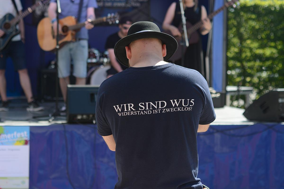 Ein Student steht mit dem Rücken zur Kamera. Er trägt einen schwarzen Hut und ein dunkles T-Shirt mit der Aufschrift: Wir sind WU 5, Widerstand ist zwecklos.